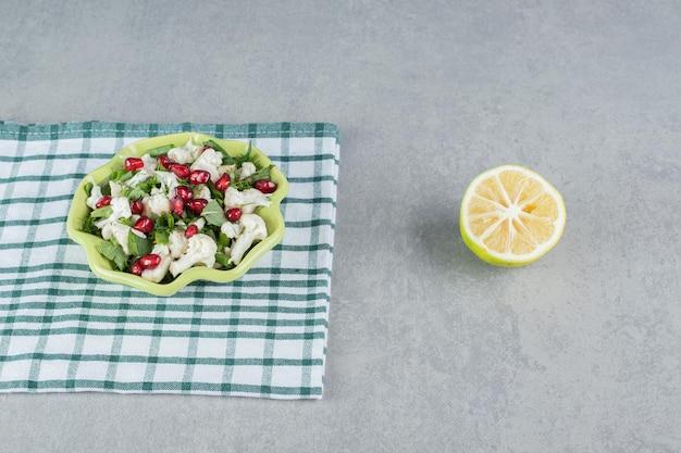 Bloemkoolsalade met rode granaatappelpitjes in een plaat.