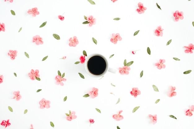 Bloemmotief gemaakt van roze hortensia bloemen, koffiekopje, groene bladeren, takken op wit