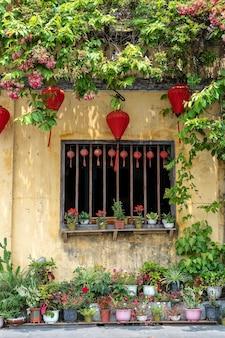 Bloempotten met bloemen, gele muur en raam met rode chinese lantaarns