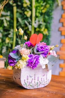 Bloemsamenstelling in kartonnen doos romige rozen lila en witte lithianthus