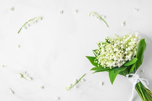 Bloemsamenstelling. lelietje-van-dalen bloemen boeket op wit marmer. plat lag. bovenaanzicht met kopie ruimte