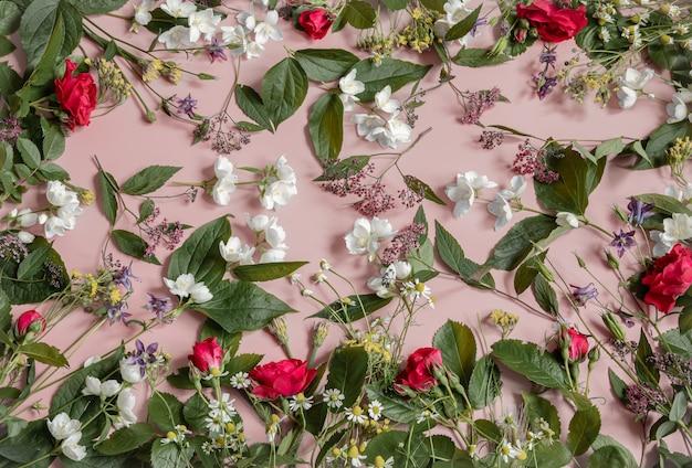 Bloemstuk met verschillende verse bloemen, bladeren en twijgen op een roze achtergrond.