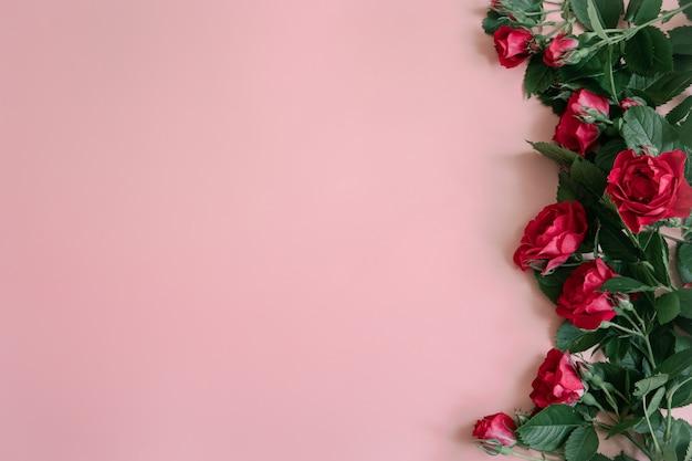 Bloemstuk met verse rode rozen op roze oppervlakte kopie ruimte