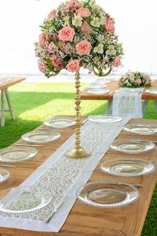 Bloemstuk op een houten tafel met glaswerk opgesteld in een tuin voor een sociaal evenement in mexico