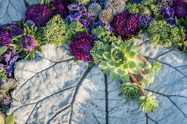 Bloemstuk van paarse asters en vetplanten