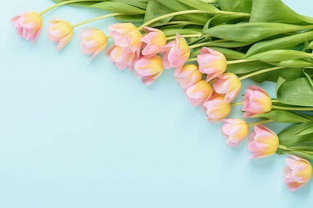 Bloemstuk van roze tulpen in de hoek op blauwe achtergrond met kopie ruimte