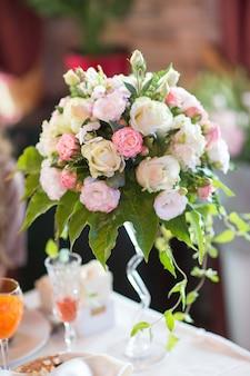 Bloemstuk van verse rozen op de tafel van een feestzaal