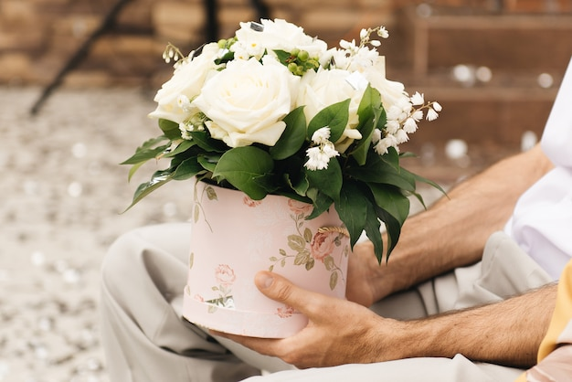 Bloemstuk voor een geschenk in de handen van een man