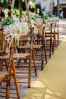 Bloemstukken voor lege stoelen voor een huwelijksceremonie in de lente
