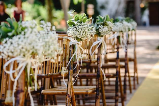 Bloemstukken voor lege stoelen voor een huwelijksceremonie in het voorjaar