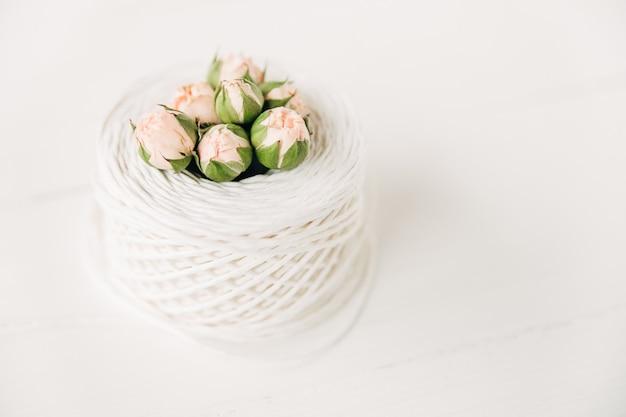 Bloemstukkleine roze roosjes met knoppenwit touwminimalistische compositie