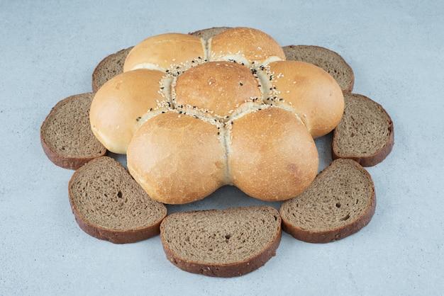 Bloemvormig brood en roggeplakken op steenoppervlak