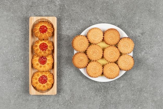 Bloemvormige koekjes met gelei en ronde crackers op borden