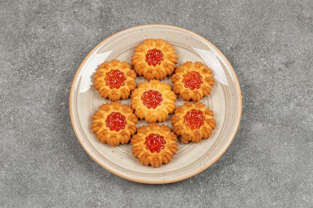 Bloemvormige koekjes met gelei op keramische plaat