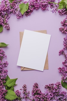 Bloesem syringa vulgaris in lila bloem en blanco papieren kaart mock-up