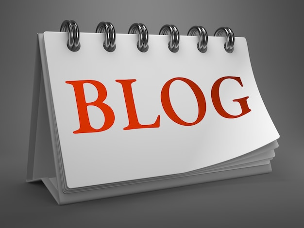 Blog - rood woord op witte bureaubladkalender geïsoleerd op grijze achtergrond.