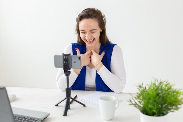 Bloggen, uitzending en mensen concept - vrouw blogger praat tegen de camera voor haar toeschouwers