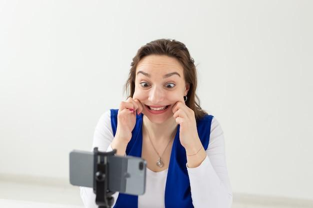 Bloggen, uitzending en mensenconcept - vrouw blogger praat met de camera voor haar toeschouwers.