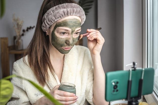 Blogger brengt een cosmetisch groen masker aan op haar gezicht op een mobiele telefoon