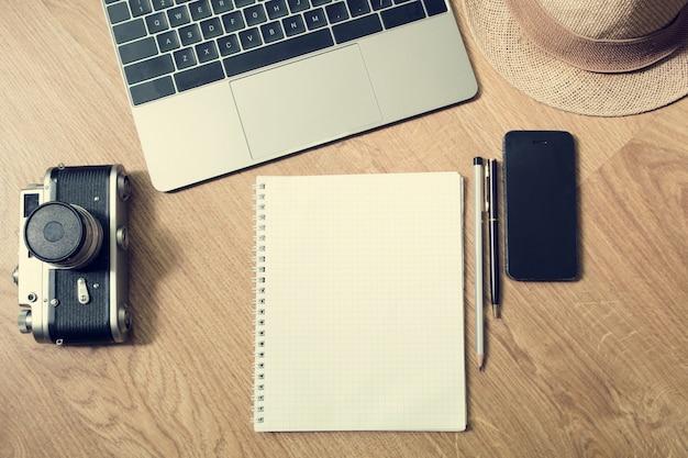 Blogger-dag. bovenaanzicht kantoor aan huis, mockup. werkruimte van de blogger vóór de vakantie - een laptop, een notebook, een pen, een potlood, een telefoon, een vintage camera, een hoed. plat leggen. vintage effect.