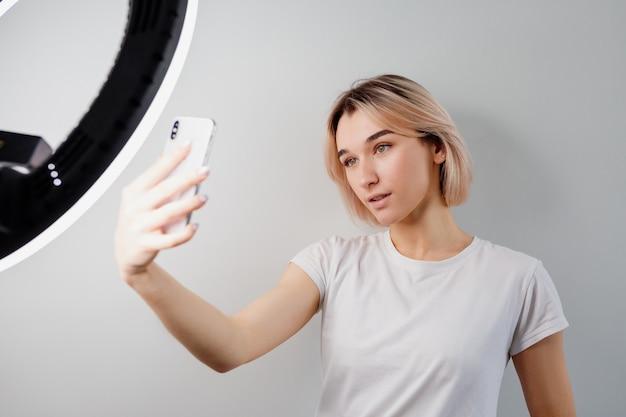 Blogger girl zendt live uit via een smartphone onder een ringlamp
