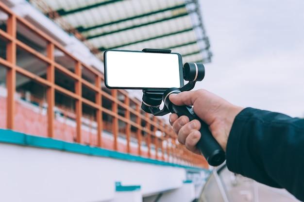 Blogger in het stadion maakt video-opnamen op een smartphone