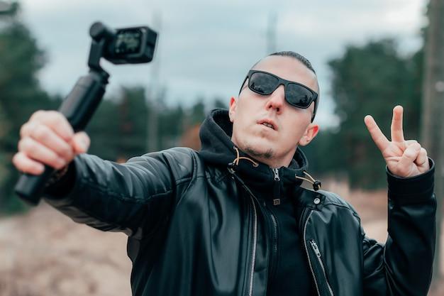 Blogger in zonnebril selfie maken of video streamen in het dennenbos met actiecamera met gimbal-camerastabilisator.
