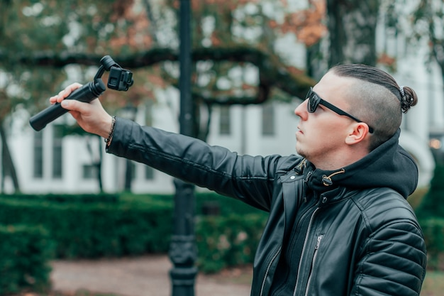 Blogger in zonnebril selfie maken of video streamen in het herfstpark met behulp van een actiecamera met gimbal-camerastabilisator.