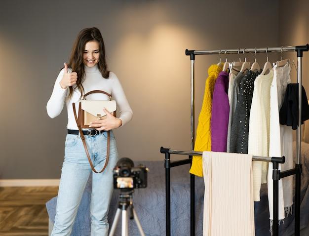 Blogger-influencermeisje met donker haar laat haar kleding zien voor haar volgers op sociale media om het online te verkopen