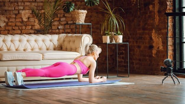 Blogger meisje doet plankmat in sport outfit met camera online training thuis, opnemen van online aërobe tutorials vanuit huis, oefenen op camera
