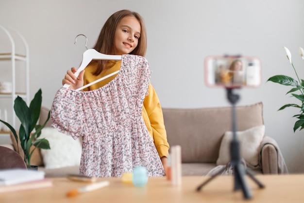 Blogger meisje praten over mode op de camera van de smartphone, jurk presenteren,