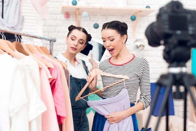 Blogger-meisjes presenteren een kleurrijke jurk aan de camera.
