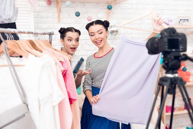 Blogger-meisjes presenteren kleurrijke jurk aan camera.