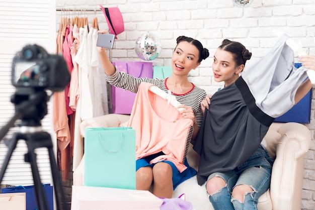 Blogger-meisjes trekken kleurrijke kleding uit tassen.