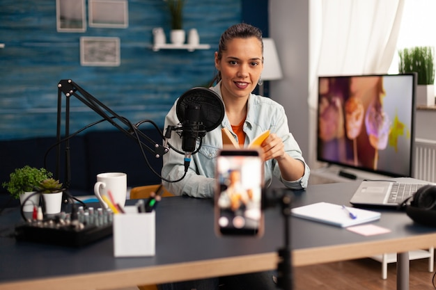 Blogger neemt boekrecensie op voor haar online talk-skow. creatieve vlogger die een videoblogconcept maakt, spreekt en kijkt naar smartphone op statief thuisstudio podcast met behulp van moderne apparatuur.