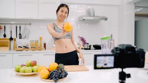 Blogger sportieve aziatische vrouw met behulp van camera-opname hoe sinaasappelsap video te maken voor haar abonnee