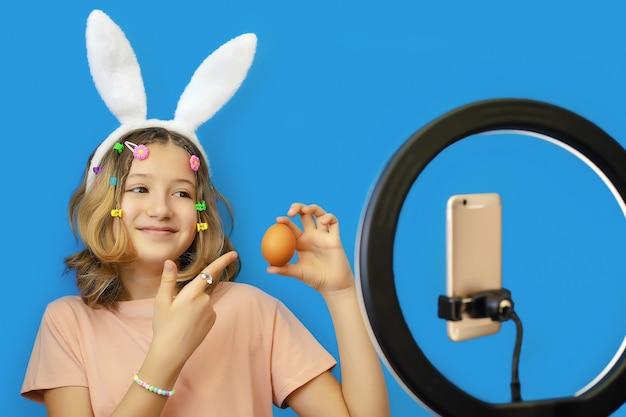 Blogger van het tienermeisje met konijnenoren op haar hoofd houdt een ei in haar handen en feliciteert haar volgers op sociale netwerken met de paasvakantie in haar smartphone