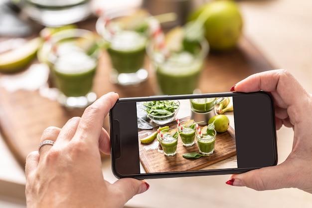 Blogger-vrouw die foto van smoothie maakt met mobiele telefoon.