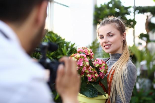 Blogger vrouw roze bloem op camera opnemen