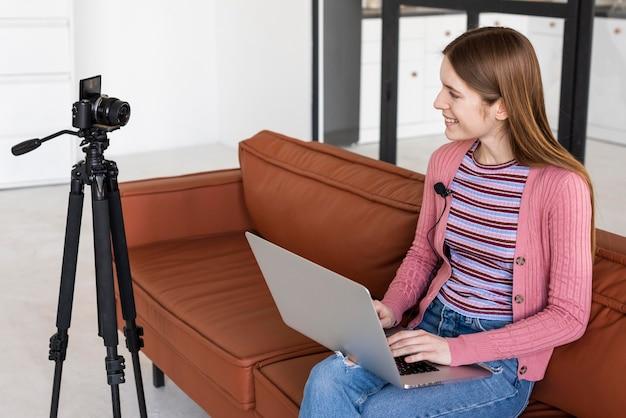 Blogger zittend op de bank met behulp van haar laptop