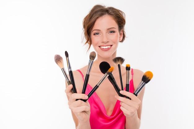 Bloggermeisje met make-upborstels op wit geïsoleerde oppervlakte