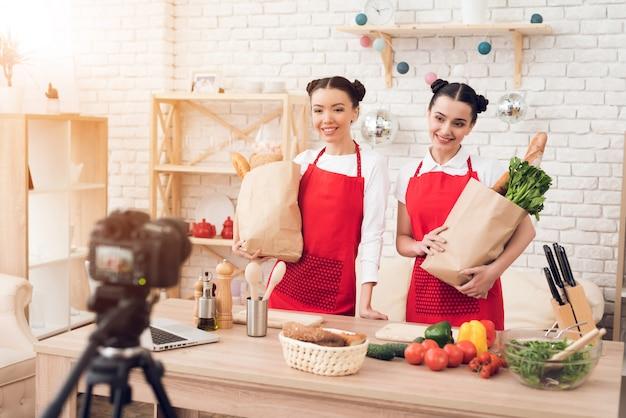 Bloggers houden verpakkingen met voedsel naar camera omhoog.