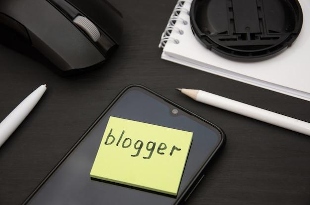 Bloggerwoord op sticker computermuis met smartphone en pen op zwart