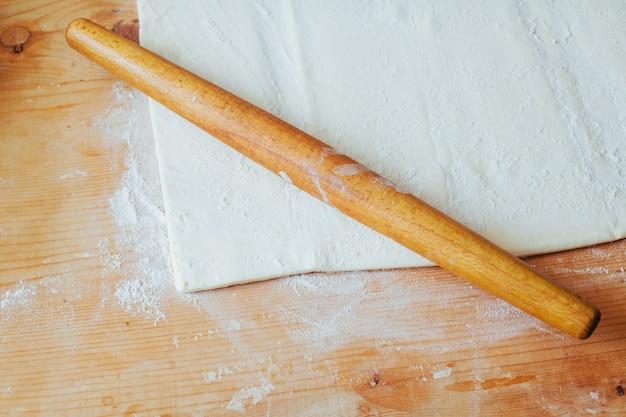 Blok van vers gemaakt gebak op een met bloem bestoven werkoppervlak met een houten deegrol
