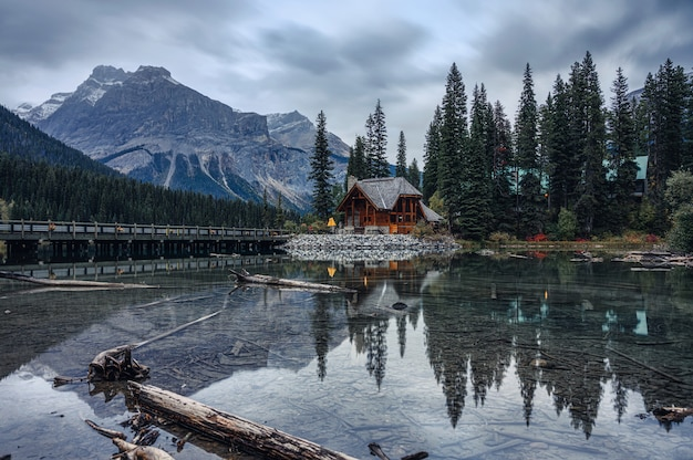Blokhuis met rotsachtige berg in dennenbos op emerald lake