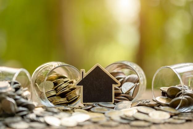 Blokhuismodel en muntstukstapel op houten lijst. geldbesparingen voor het huisconcept
