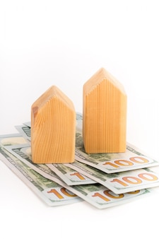 Blokhuismodel met dollarsbankbiljetten, onroerende goederenconcept