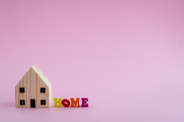 Blokhuismodel met huisalfabet op roze achtergrond voor huisvestingsconcept