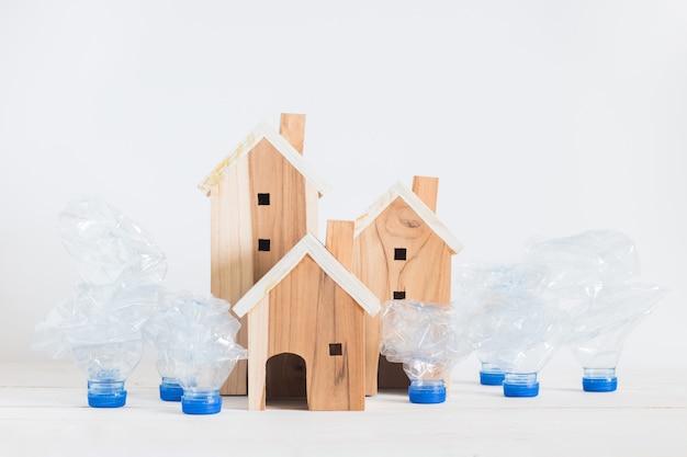 Blokhuismodel met huisvuil kringloop plastic flessen die op witte houten raad, globale verwarmende oplossing plaatsen.