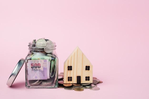 Blokhuismodel met thaise muntbankbiljet en geldmuntstukken in de glaskruik voor bedrijfs, financiën en bezitsinvesteringenconcept